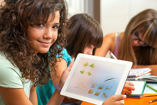 Cute girl showing homework on tablet.